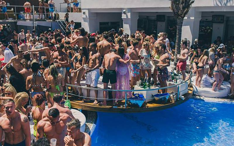People stood and dancing around the pool at Sisu