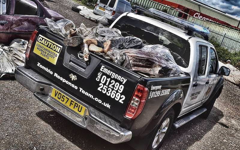 Fake bodies in the trunk of a truck, with zombie stickers on