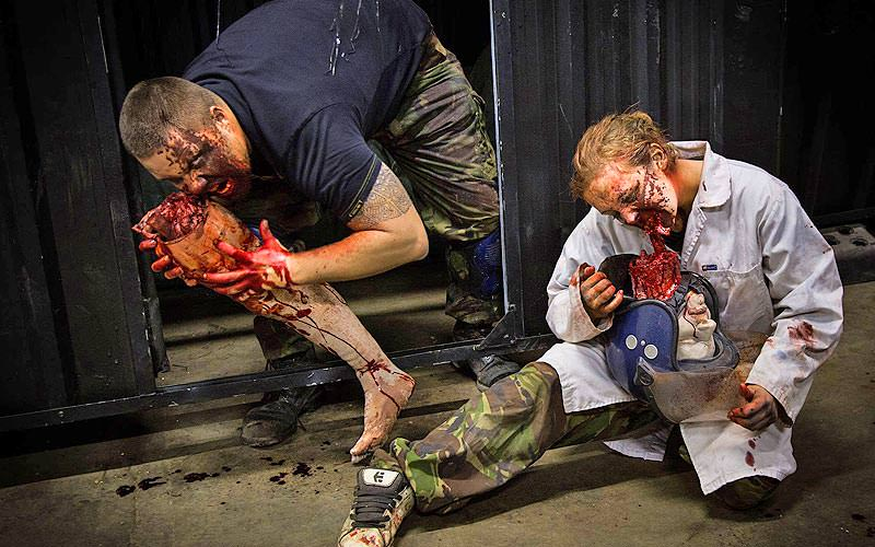 Two people dressed up as zombies and eating fake body parts