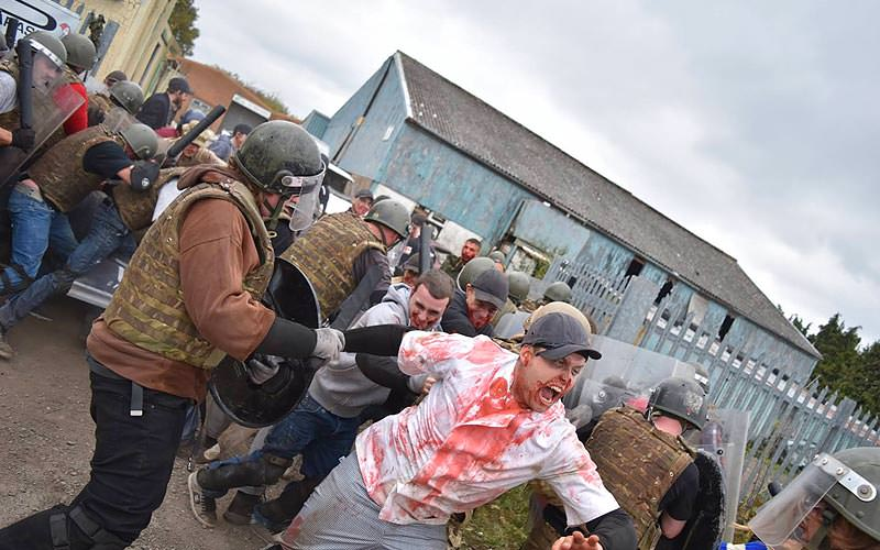 Someone dressed as a zombie, with people in camouflage gear attempting to stop them
