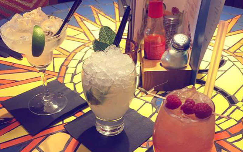 Five tiled images of cocktails and one burger