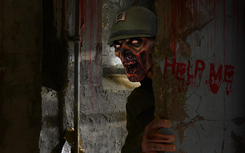 A man dressed up as a zombie, hiding behind a wall