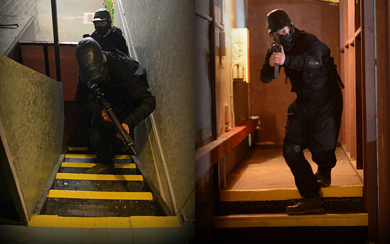 IMage of men coming up the yellow painted stairs and a man coming down the stairs pointing the gun at the camera.