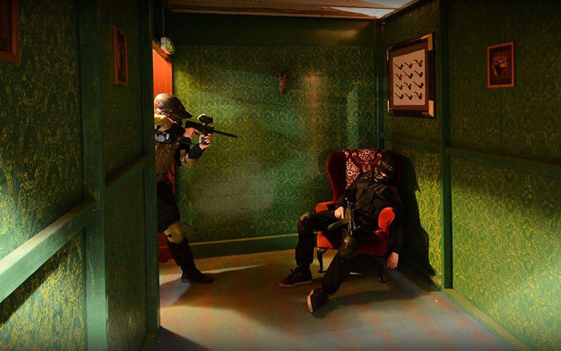 Image of man pointing his airsoft gun at man sitting in chair, in a green room.