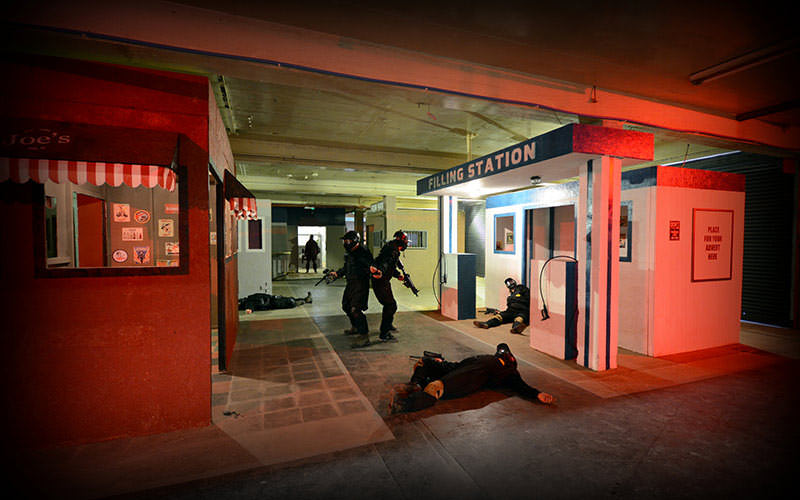 Image of two men looking around pop up buildings with a couple of men lying on the ground.