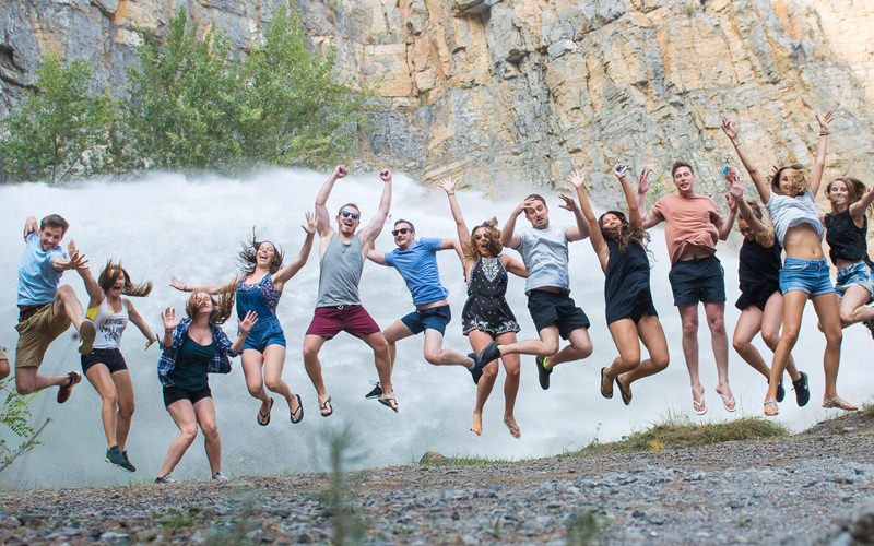 A group of people jumping in front of a hot spring