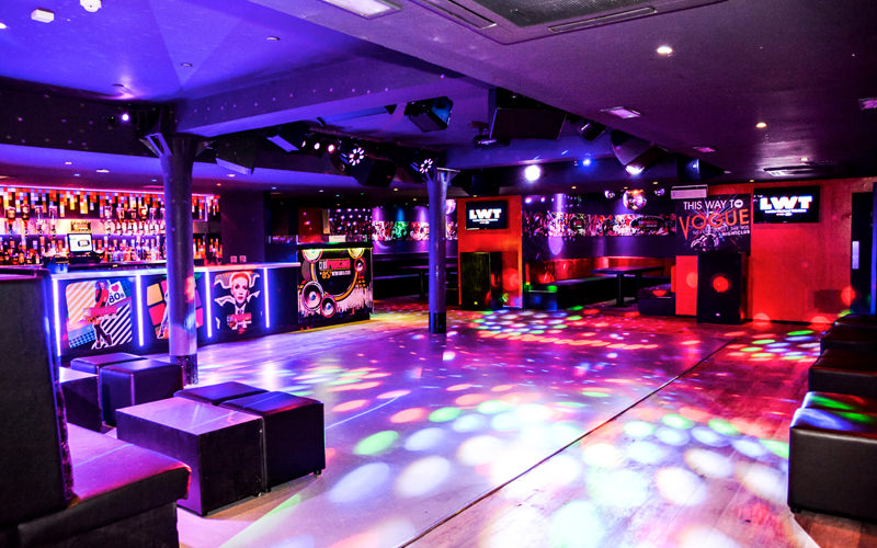 A large dance floor with strobe lighting and a bar in the background