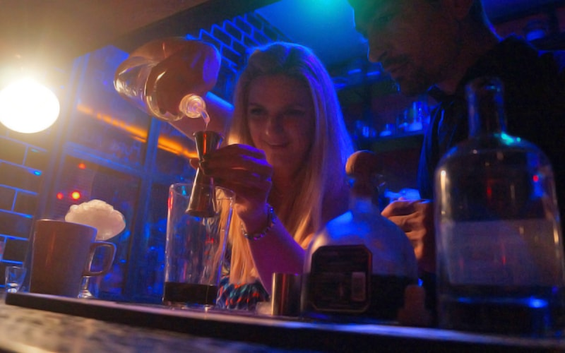 A blonde girl pouring a shot into a spirit measurer