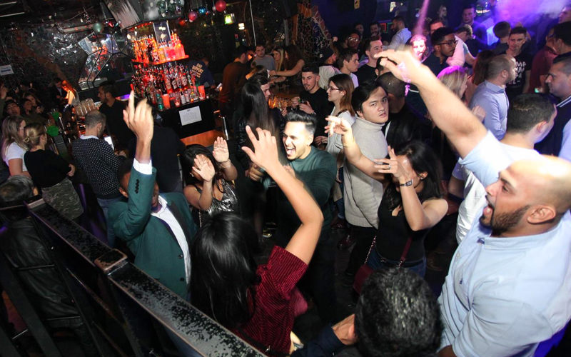 A group of people jumping in a nightclub