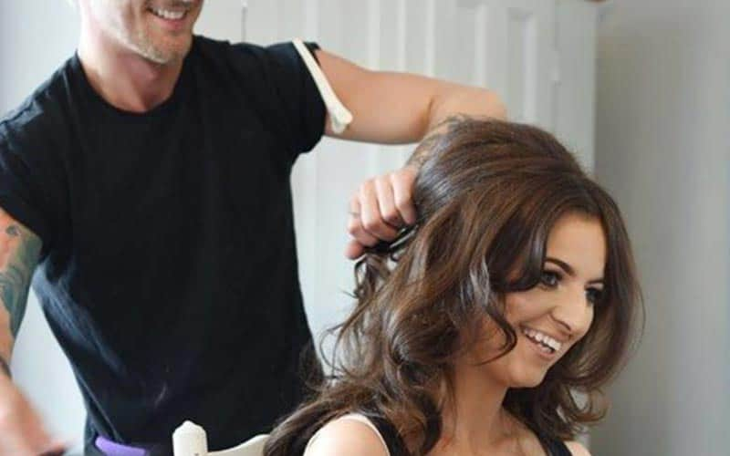 A male hairdresser, styling the hair of a brunette woman