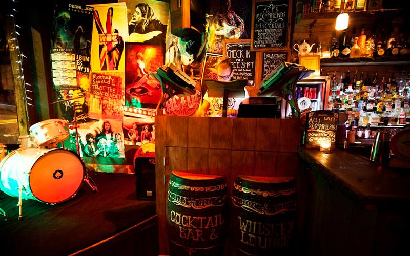 Image of the dj area in smokin aces with beer barrels as part of the dj box and art work placed around the walls