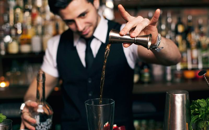 Image of a bar tender pouring a spirit from a measure into a glass