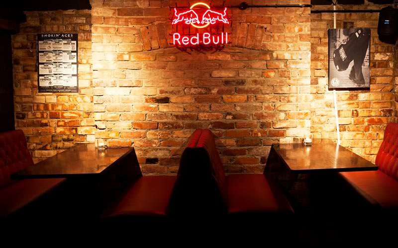 Image of a seating area in smokin aces with tables attached to the brick wall with red leather chesterfield seating and a red neon red bull light in the middle of the wall