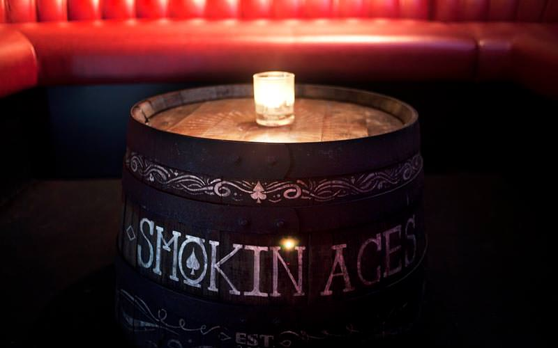 Close up image of a beer barrel being used as a table with smokin aces written in white pen with a small candle placed in the middle of the table