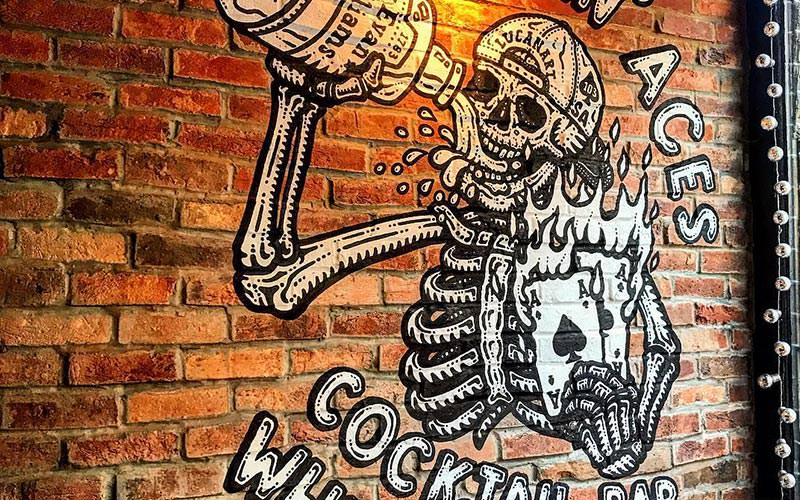 Image of a brick wall with a skeleton wearing a baseball cap backwards and drinking whiskey with the smokin aces sign painted on the wall