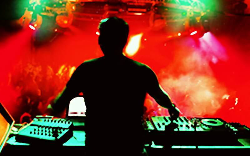 A DJ performing to a crowd under red and green lighting