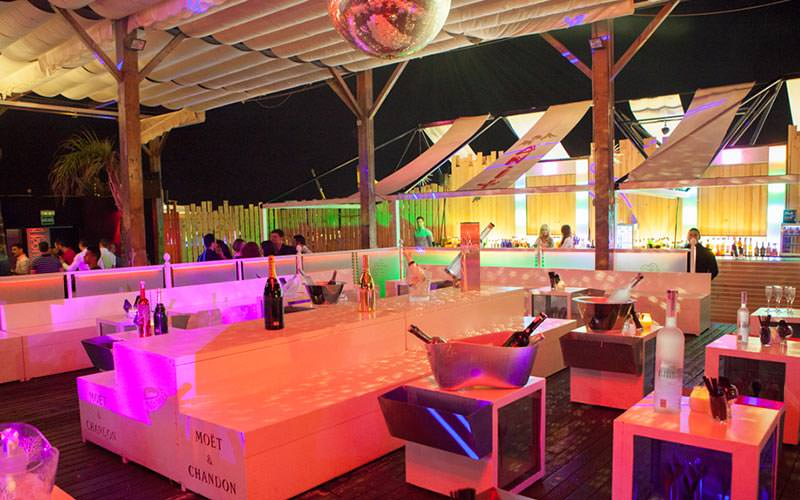 An outdoor terrace with champagne bottles chilling on the tables, under a disco ball on the ceiling