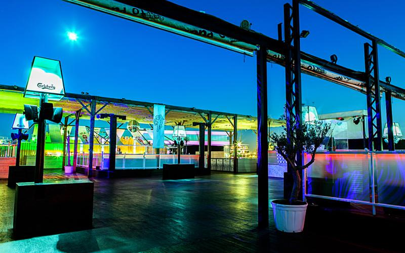 The outdoor terrace of a club, with neon lights illuminating the area