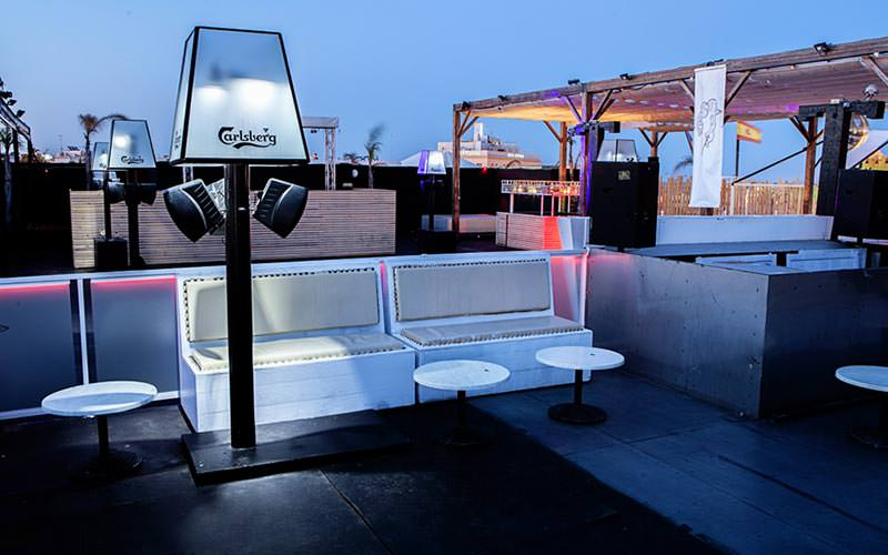 An outdoor drinking terrace with Carlsberg embellished lamps