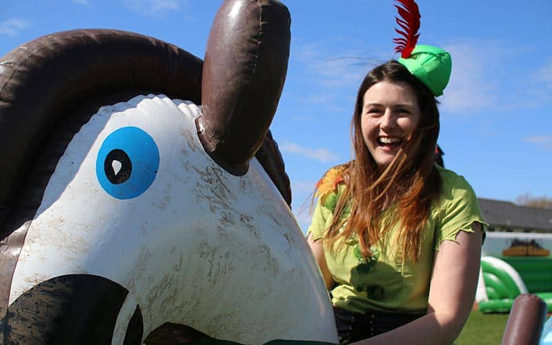 A woman dressed as robin hood riding an inflatable horse