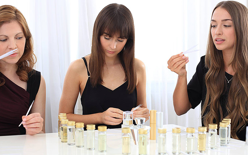 Three women sniffing perfume sticks in front of perfume bottles on a table