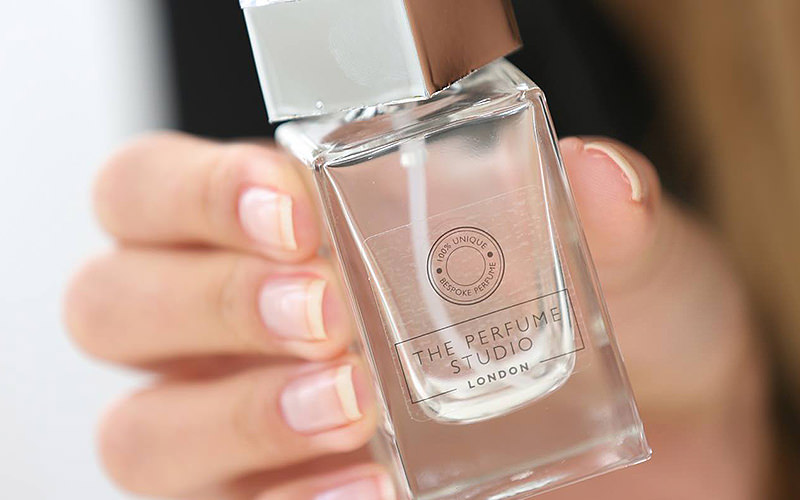 A woman's hands holding a clear perfume bottle