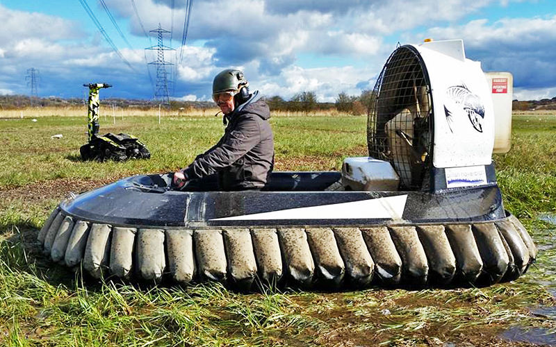 Man riding small hovercraft over marshy grassland
