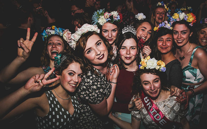 A group photo of women with flower crowns on, at Thekla nightclub