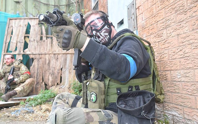 Man in militia style combat gear and face mask aims an airsoft gun