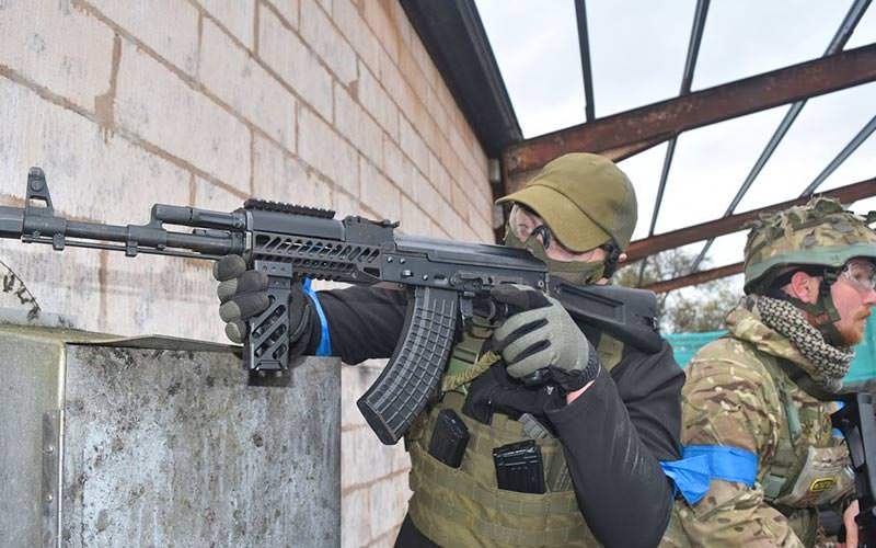 Man aims an airsoft AK-47 replica round a corner in urban setting