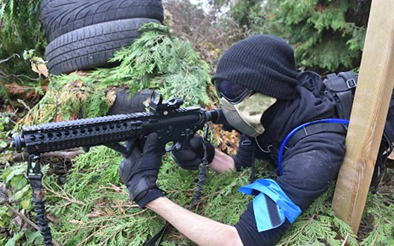 man in black military gear aims airsoft rifle from foliage cover