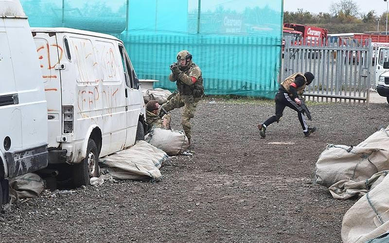 Men in combat gear use vans for cover in airsoft game