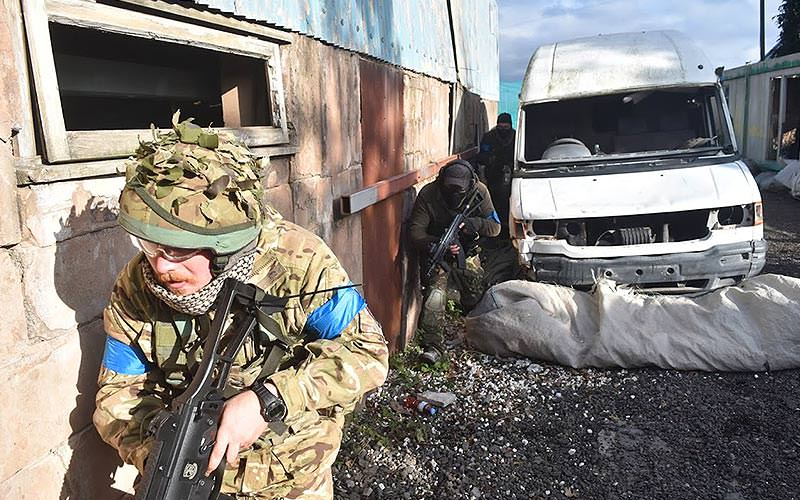 men taking part in airsoft game run through warfare setting