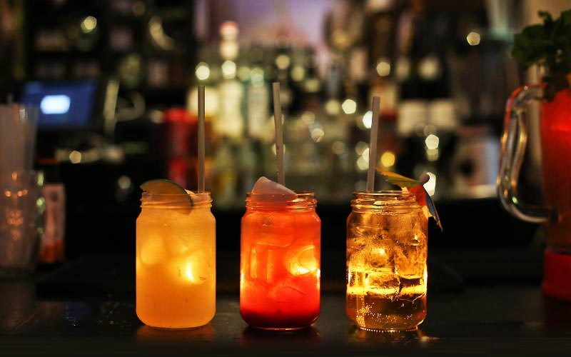 A line of three cocktails on top of a bar, in jam jars