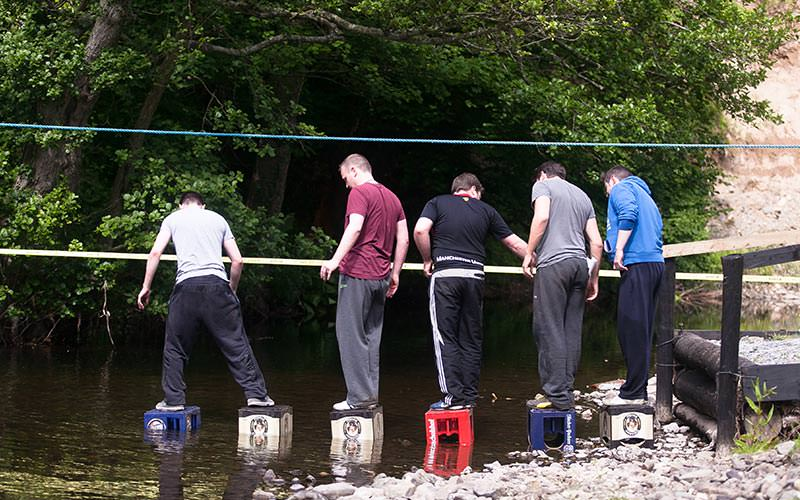 Five men using a rope to guide them over some crates on a river