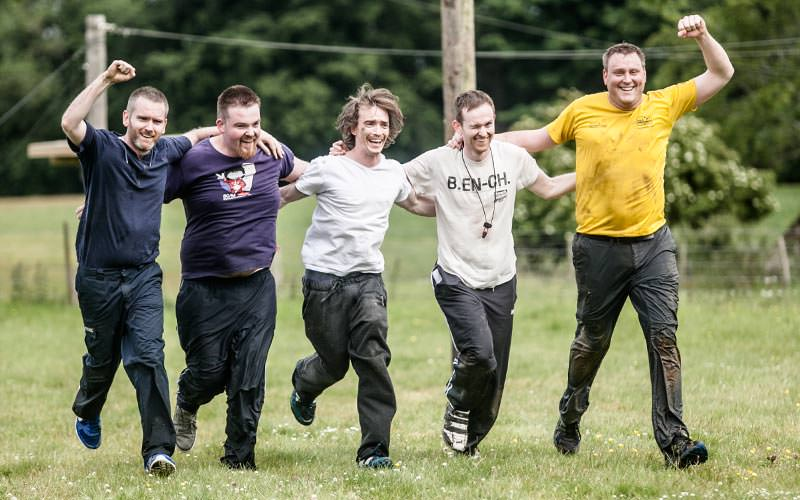 Five men celebrating victory by running in a field