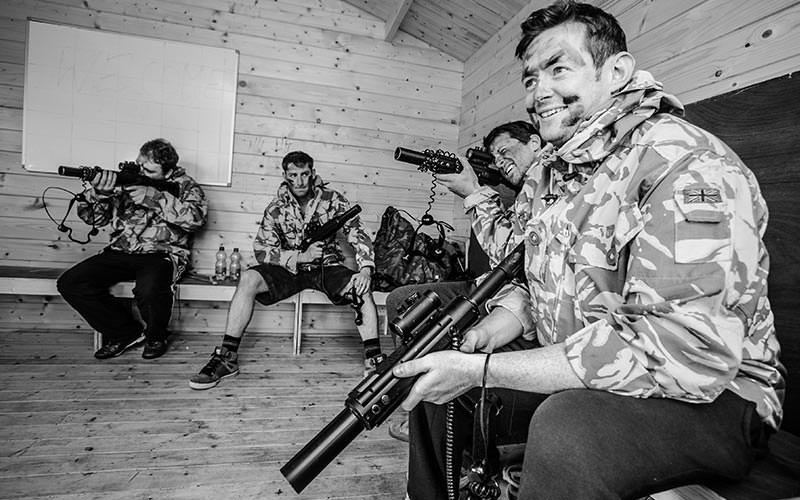 A black and white image of men in a hut wearing camouflage
