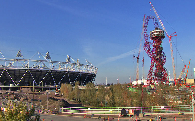 The Slide at ArcelorMittal Orbit in London being constructed on a sunny day, with the London Stadium sitting next to it