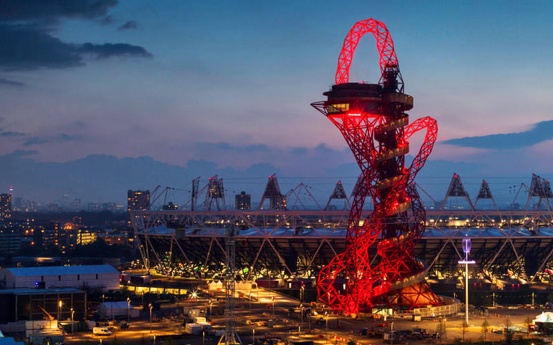 The Slide at ArcelorMittal Orbit in London lit up red in the nights sky, with London stadium in the background