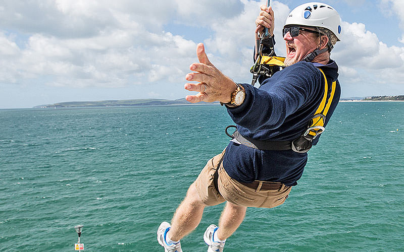 A man flying over the sea on a PierZip line
