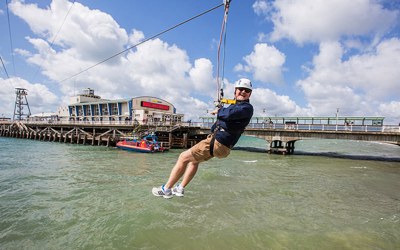 A man zipwiring with Bournemouth Pier in the background