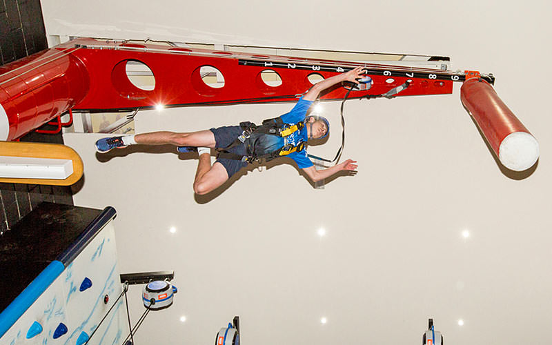 A man doing a leap of faith challenge indoors