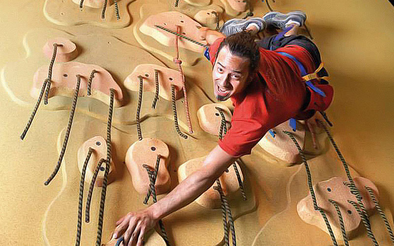 A man climbing on a climbing wall