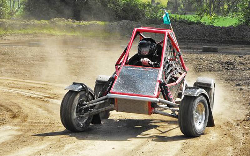 A man driving in a red rage buggy