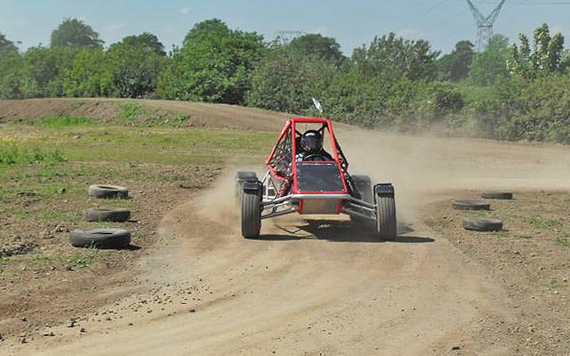 A man driving in a red rage buggy, with tyres on the side of the course