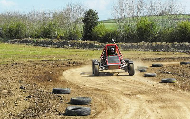 A man driving a red rage buggy on a dirt track