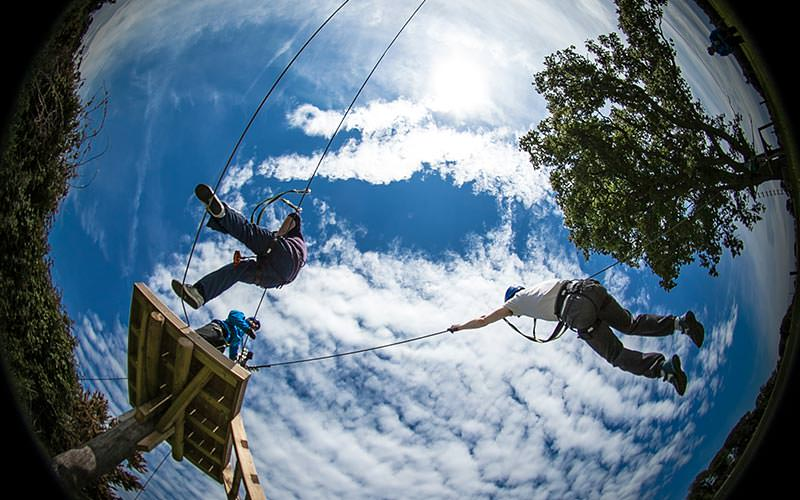 A fish eye photo of people climbing high ropes