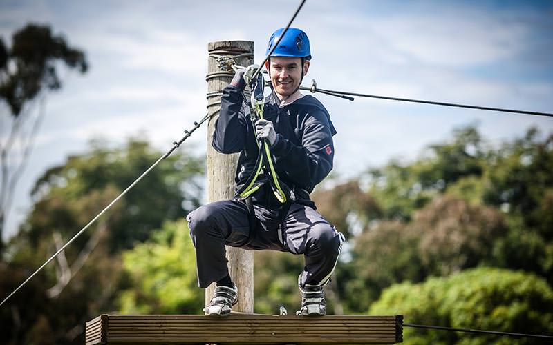 A man waiting to jump off a high ropes course