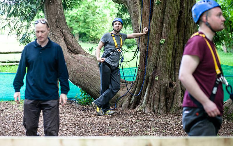 Three men participating in high ropes