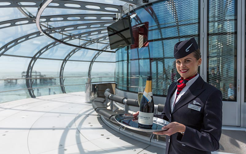A waitress in British Airways i360 holding some Champagne